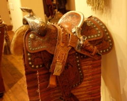 Historic saddle with holster and revolver in living room