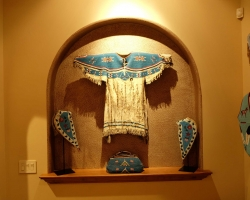 Beadwork: Woman's beaded shirt, pair of tapaderos, beaded bag.  To the side a beaded vest and a pair of beaded gauntlets.